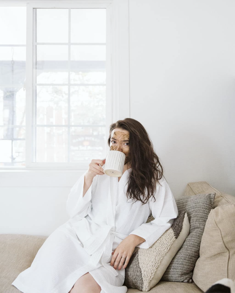 hayley wood sipping tea in a bathrobe while wearing a mask for maskne.